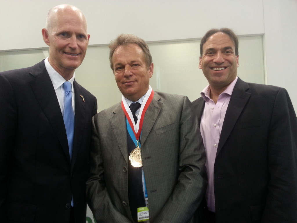 Florida Governor Rick Scott, Vision Systems President and CEO Carl Putman, and Research Frontiers President and CEO Joseph M. Harary